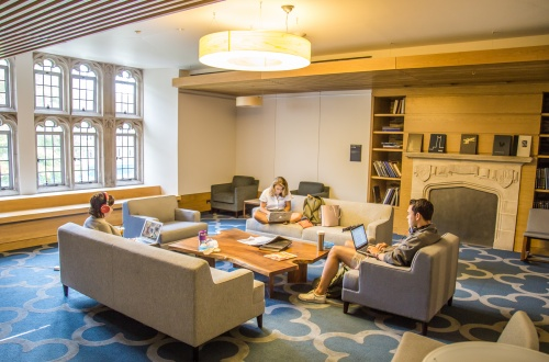 Photo of Brodhead Center Chaplin Family Study Room showing couches, armchairs, coffee table, windows, and three people studying