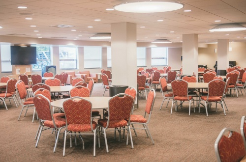 Large room with multiple banquet tables and chairs