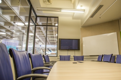 Photo of Bryan Center Griffith Board Room showing conference table chairs, projection screen, and whiteboard