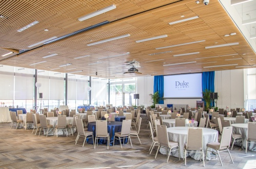 Photo of Penn Pavilion Room showing round tables, chairs, stage, windows, and projection screen.