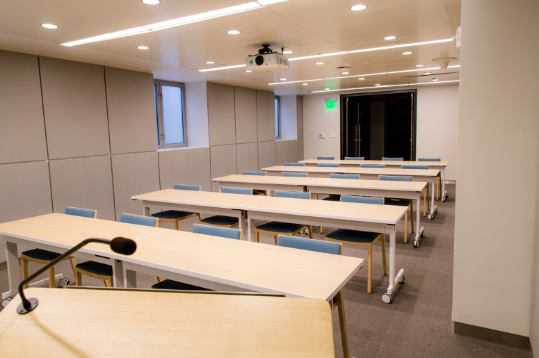 Photo of Brodhead Center Room 067 from the front of the room showing the lectern, tables, and chairs