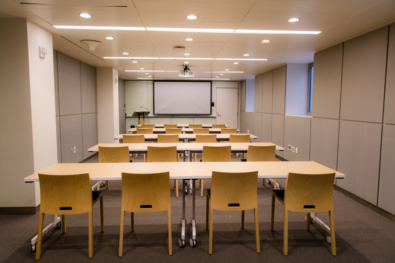 Photo of Brodhead Center Room 067 from the back of the room showing tables, chairs, and front of room