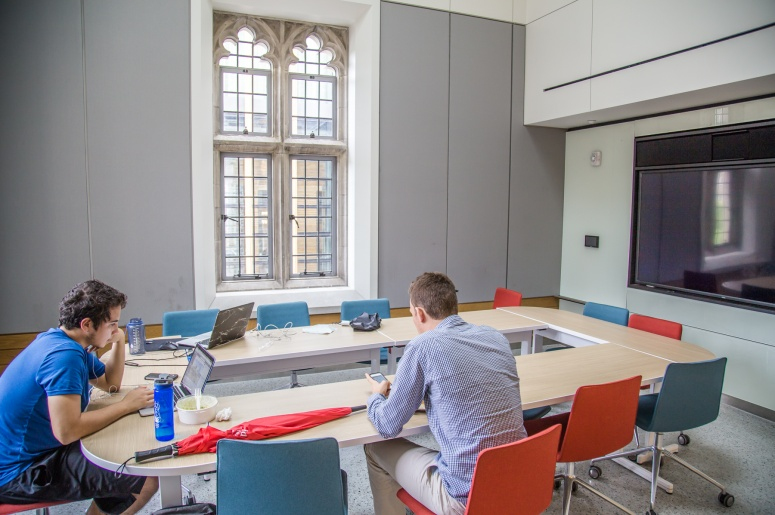Photo of Brodhead Center Room 248 showing conference table, chairs, projection screen, window, and two people at table