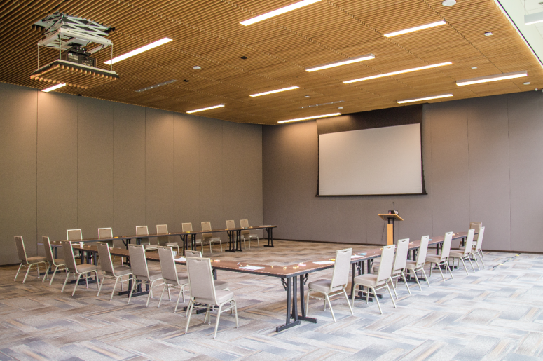 Penn Event Set Up 2 with tables and chairs surrounding a large projection screen